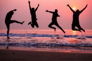 People jumping in air by ocean