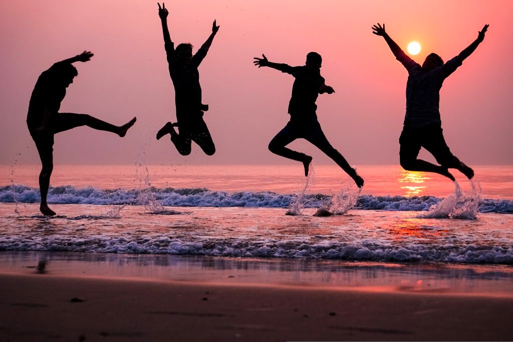 People jumping in air by ocean