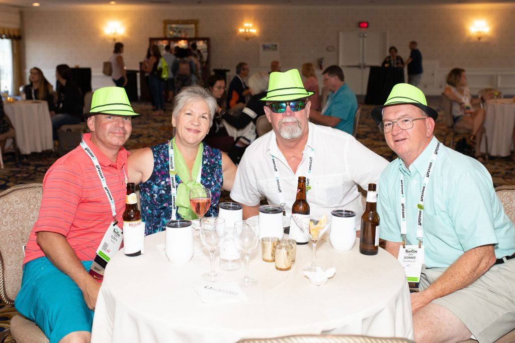 4 people sitting at a table wearing lime green hats